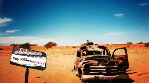 Junk car sitting in a desert with an i Buy Junk Vehicles sign beside it