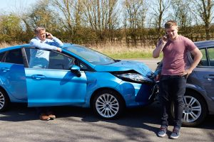 Drivers Making Phone Call in Front of Their Wrecked Cars after Traffic Accident