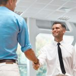 man shaking hands with used car buyer