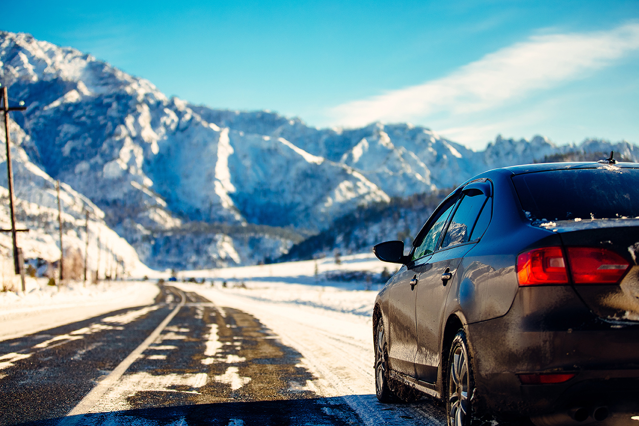 used vehicle driving on snowy mountain road